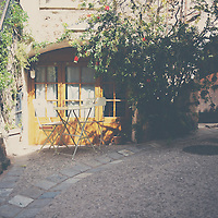 a table and chairs sitting outside a french home on a quiet street in St Guilheim le Desert.