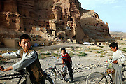 Young boys are going back home after a visit to the bazaar passing by some of the caves in Bamyian that are still inhabited by a mixture of IDP (Internally-Displaced Persons) returnees and others with no chances for a better home. The Buddhas of Bamiyan were two 6th century monumental statues of standing Buddhas carved into the side of a cliff in the Bamiyan valley in the Hazarajat region of central Afghanistan, situated 230 km northwest of Kabul at an altitude of 2500 meters. The statues represented the classic blended style of Gandhara art. The main bodies were hewn directly from the sandstone cliffs, but details were modelled in mud mixed with straw, coated with stucco. Amid widespread international condemnation, the smaller statues (55 and 39 meters respectively) were intentionally dynamited and destroyed in 2001 by the Taliban because they believed them to be un-Islamic idols. Once a stopping point along the Silk Road between China and the Middle East, researchers think Bamiyan was the site of monasteries housing as many as 5,000 monks during its peak as a Buddhist centre in the 6th and 7th centuries. It is now a UNESCO Heritage Site since 2003. Archaeologists from various countries across the world have been engaged in preservation, general maintenance around the site and renovation. Professor Tarzi, a notable An Afghan-born archaeologist from France, and a teacher in Strasbourg University, has been searching for a legendary 300m Sleeping Buddha statue in various sites between the original standing ones, as documented in the old account of a renowned Chinese scholar, Xuanzang, visiting the area in the 7th century. Professor Tarzi worked on projects to restore the other Bamiyan Buddhas in the late 1970s and has spent most of his career researching the existence of the missing giant Buddha in the valley.
