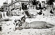 smiling young adult woman laying on the beach France 1933