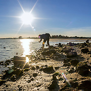 People enjoying spring sunset time in Quatro-Aguas East beach, Ria Formosa Natural Reserve, at Tavira. Algarve, Portugal.