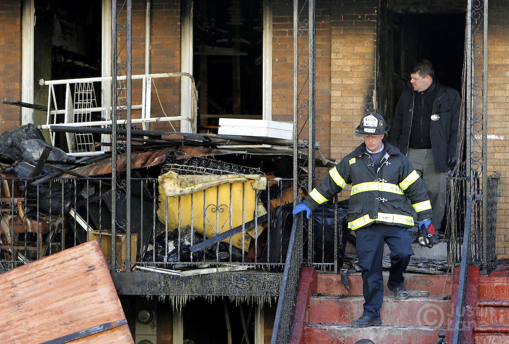 New York City firefighters exit a house where 9 people were killed, 8 of them children, in an overnight fire in the Bronx, New York on Thursday 08 March 2007.