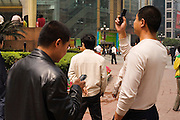 Men on their mobiles, Chongqing, The People's Republic of China