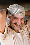 Akbar Zareh takes a break from the hectic schedule at his bakery in the province of Yazd, Iran to fix his head scarf. (Featured in the book What I Eat: Around the World in 80 Diets.) MODEL RELEASED.