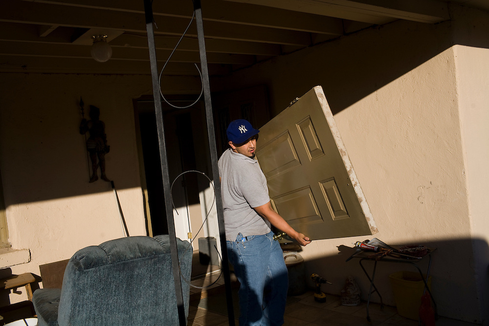Larry Martinez works on weatherizing a home.  He works for the Community Action Agency(CAA). The CAA received stimulus funding and, among other things, works on weatherizing the homes of poor families and individuals in New Mexico.