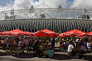 Spectators eat beneath Coca-Cola branded sponsor brolleys in near the main stadium in the Olympic Park during the London 2012 Olympics. Coca-Cola Company has supported the Olympic Games began in 1928, now a 92 years association without interruption. This land was transformed to become a 2.5 Sq Km sporting complex, once industrial businesses and now the venue of eight venues including the main arena, Aquatics Centre and Velodrome plus the athletes' Olympic Village. After the Olympics, the park is to be known as Queen Elizabeth Olympic Park.