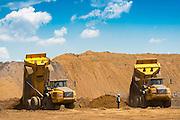 Mining dump trucks tipping sand