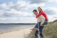 Man giving woman piggy back at beach