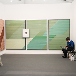 London, UK - 15 October 2014: an exhibitor works on his laptop at the Frutta Gallery during the first day of Frieze Art Fair and Frieze Masters in Regent's Park.