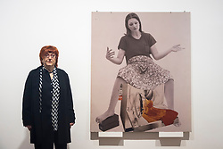 "© Licensed to London News Pictures. 28/11/2019. LONDON, UK. Austrian artist Valie Export poses with ""Die Geburtenmadonna"", 1976, at the preview of her exhibition ""The 1980 Venice Biennale Works"" at Galerie Thaddeus Ropac in Mayfair.  The exhibition comprises innovative multimedia installation from the 39th Venice Biennale and 17 large-scale photographs mounted on wooden panels from her important photographic series Body Configurations (1972–82).  The show runs 28 November to 25 January 2020.  Photo credit: Stephen Chung/LNP"