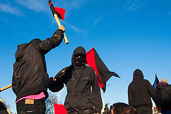 London, March 7th 2015. Following the Climate march through London, masked anarchists and environmental activists clash with police following a breakaway protest at Shell House. PICTURED: Anarchists with their flags outside Parliament as they march towards Shell House.