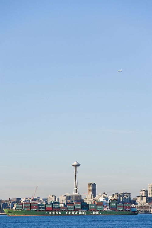 A ship full of containers on Elliott Bay below the Space Needle.  An airplane in the air above Seattle, WA USA.