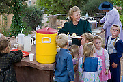 "Aug 9, 2008 -- COLORADO CITY, AZ: Members of the Jessop family, a polygamist family and members of the FLDS, serve cobbler deserts during a picnic at the Jessop home in Colorado City, AZ. Colorado City and neighboring town of Hildale, UT, are home to the Fundamentalist Church of Jesus Christ of Latter Day Saints (FLDS) which split from the mainstream Church of Jesus Christ of Latter Day Saints (Mormons) after the Mormons banned plural marriage (polygamy) in 1890 so that Utah could gain statehood into the United States. The FLDS Prophet (leader), Warren Jeffs, has been convicted in Utah of ""rape as an accomplice"" for arranging the marriage of teenage girl to her cousin and is currently on trial for similar, those less serious, charges in Arizona. After Texas child protection authorities raided the Yearning for Zion Ranch, (the FLDS compound in Eldorado, TX) many members of the FLDS community in Colorado City/Hildale fear either Arizona or Utah authorities could raid their homes in the same way. Older members of the community still remember the Short Creek Raid of 1953 when Arizona authorities using National Guard troops, raided the community, arresting the men and placing women and children in ""protective"" custody. After two years in foster care, the women and children returned to their homes. After the raid, the FLDS Church eliminated any connection to the ""Short Creek raid"" by renaming their town Colorado City in Arizona and Hildale in Utah. A member of the Jessop family weeds the community corn plot in Colorado City, AZ. The Jessops are a polygamous family and members of the FLDS. Photo by Jack Kurtz / ZUMA Press"