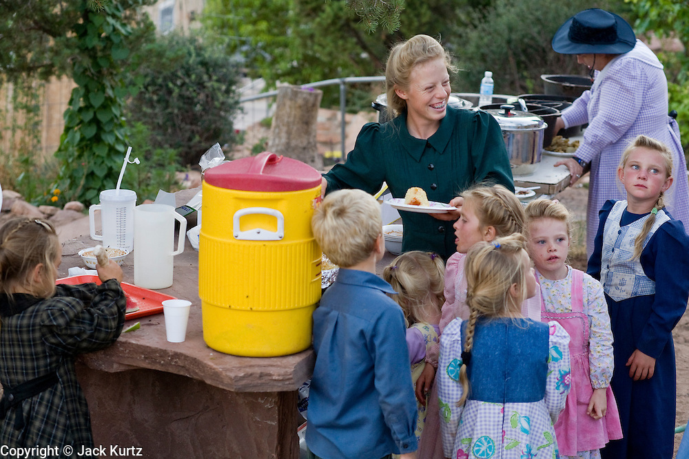 """Aug 9, 2008 -- COLORADO CITY, AZ: Members of the Jessop family, a polygamist family and members of the FLDS, serve cobbler deserts during a picnic at the Jessop home in Colorado City, AZ. Colorado City and neighboring town of Hildale, UT, are home to the Fundamentalist Church of Jesus Christ of Latter Day Saints (FLDS) which split from the mainstream Church of Jesus Christ of Latter Day Saints (Mormons) after the Mormons banned plural marriage (polygamy) in 1890 so that Utah could gain statehood into the United States. The FLDS Prophet (leader), Warren Jeffs, has been convicted in Utah of """"rape as an accomplice"""" for arranging the marriage of teenage girl to her cousin and is currently on trial for similar, those less serious, charges in Arizona. After Texas child protection authorities raided the Yearning for Zion Ranch, (the FLDS compound in Eldorado, TX) many members of the FLDS community in Colorado City/Hildale fear either Arizona or Utah authorities could raid their homes in the same way. Older members of the community still remember the Short Creek Raid of 1953 when Arizona authorities using National Guard troops, raided the community, arresting the men and placing women and children in """"protective"""" custody. After two years in foster care, the women and children returned to their homes. After the raid, the FLDS Church eliminated any connection to the """"Short Creek raid"""" by renaming their town Colorado City in Arizona and Hildale in Utah. A member of the Jessop family weeds the community corn plot in Colorado City, AZ. The Jessops are a polygamous family and members of the FLDS. Photo by Jack Kurtz / ZUMA Press"""