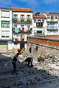 Workmen restoring paving stones in cobbled street in Castro Urdiales in Cantabria, Northern Spain