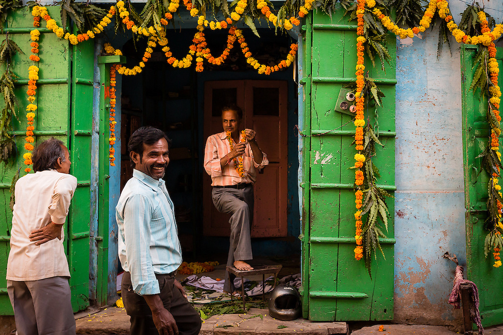 Theree men prepare the front of the house for Diwali, the Hindu Festival of Light, by hanging flowers on the entrance.