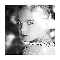 Young girl with blonde hair looking over shoulder at camera