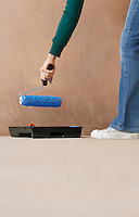 Woman painting wall with paint roller low section