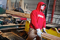 """Kyle Hudson places a rough-cut board onto a conveyor Tuesday, Feb. 28 after the section was cut by a large circular saw blade. Whiteman Lumber Company's use of a circular saw blade is a rarity compared to bandsaws, but a necessity since the sawmill's clients prefer the """"rough cut"""" look for building materials."""
