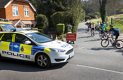 © Licensed to London News Pictures. 10/04/2020. Dorking, UK. Police look on as cyclists stop at a closed road at Surrey beauty spot Box Hill near Dorking. Police have closed Box Hill over the Easter Weekend to stop the spread of the coronavirus . The government has warned that people must continue to follow the public health guidance over the Easter weekend. Photo credit: Peter Macdiarmid/LNP
