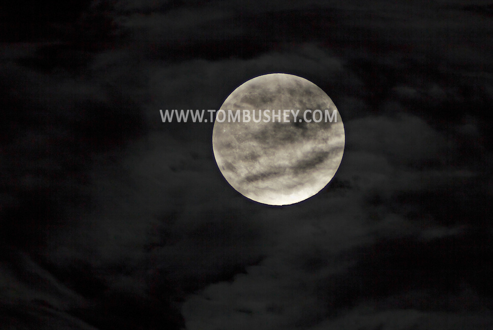 Middletown, New York - The full moon shines through clouds in the eastern sky on Sept. 8, 2014. The full moon of September was the third straight supermoon in 2014.