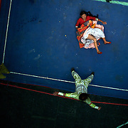 Yolanda La Amorosa lies on the canvas while fighting her male counterpart during the 'Titans of the Ring' wrestling group's Sunday performance at El Alto's Multifunctional Centre. Bolivia. The wrestling group includes the fighting Cholitas, a group of Indigenous Female Lucha Libra wrestlers who fight the men as well as each other for just a few dollars appearance money. El Alto, Bolivia, 14th March  2010. Photo Tim Clayton