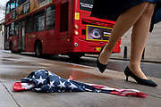 As a red London bus passes-by, a pair of legs walk past an American Stars and Stripes flag bandana lying on the wet pavement in the City of London, the UK capital's financial district, on 17th August 2020, in the City of London, England.