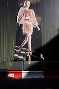 Two elderly pedestrians pass beneath a giant billboard featuring a catwalk model weaing haute couture.