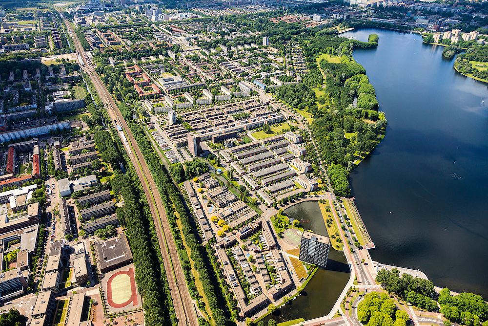 Nederland, Noord-Holland, Amsterdam, 14-06-2012; Overzicht van de wijk Slotervaart, met onder in beeld de nieuwbouwwijk Oostoever, met waterpartij, op de plaats van de voormalige rioolwaterzuivering West. Rechtsonder de Sloterplas, diagonaal de ringspoorbaan. Links van de spoorbaan Overtoomse Veld...De wijken zijn onderdeel van de Westelijke Tuinsteden, gerealiseerd op basis van het Algemeen Uitbreidingsplan voor Amsterdam (AUP, 1935). Voorbeeld van het Nieuwe Bouwen, open bebouwing in stroken, langwerpige bouwblokken afgewisseld met groenstroken. ..View on one of the western garden cities of Amsterdam Slotervaart.  Constructed on the basis of the General Extension Plan for Amsterdam (AUP, 1935). Example of the New Building (het Nieuwe Bouwen), detached in strips, oblong housing blocks alternated with green areas, built in fifties and sixties of the 20th century. Recreational lake Sloterplas (r)  and  new constructed residential district.(bottom picture)..luchtfoto (toeslag), aerial photo (additional fee required).foto/photo Siebe Swart