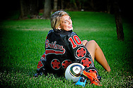 Young lady sitting in the grass with back turned showing off her letter jacket with her soccer ball and colored shoes.