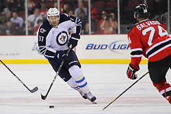 Jan 17; Newark, NJ, USA; Winnipeg Jets right wing Eric Fehr (17) skates with the puck while being defended by New Jersey Devils defenseman Bryce Salvador (24) during the first period at the Prudential Center.