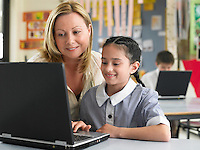 Teaching sitting with elementary schoolgirl using laptop in classroom