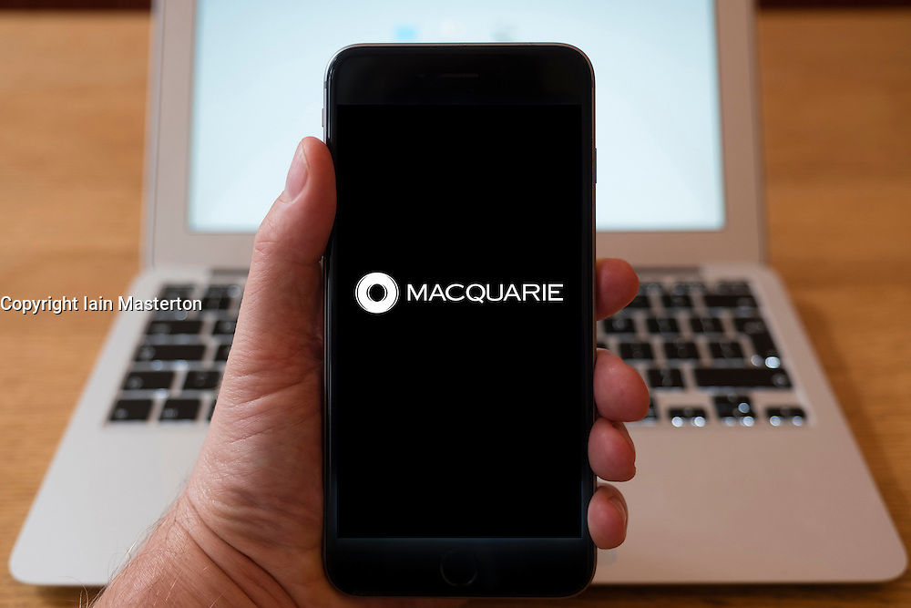 Using iPhone smart phone to display website logo of Macquarie a global investment banking and diversified financial services group