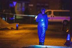 © Licensed to London News Pictures. 19/12/2019. London, UK. A forensic investigator searches for evidence on Courtland Avenue after reports of a fight, two men were later found a short distance from the scene with stab wounds, one of the victims later died. Police were called to Courtland Avenue, NW7, at 20:11GMT following a report of a fight in progress. Officers attended however no trace of any victim or suspects was found. At 20.27GMT, police were called by the London Ambulance Service to Barnet Bypass, near Scratchwood Park, to reports of a man, in his 20s, with stab injuries. Officers attended. The man was treated at the scene by paramedics before being taken to hospital. After a search of a car found at the scene, a man, in his 30s, was found inside a vehicle with stab wounds. Despite the efforts of emergency services, he was declared dead a short time later.. Photo credit: Peter Manning/LNP