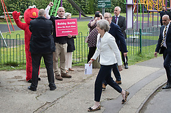 © Licensed to London News Pictures. 08/06/2017. Sonning, UK. Prime Minister Theresa May and her husband Philip pass rights campaigner Bobby Smith and his Elmo character as they arrive at thier local polling station to cast there vote in the general election. Polling stations are open from 7am - 10pm.  Photo credit: Peter Macdiarmid/LNP