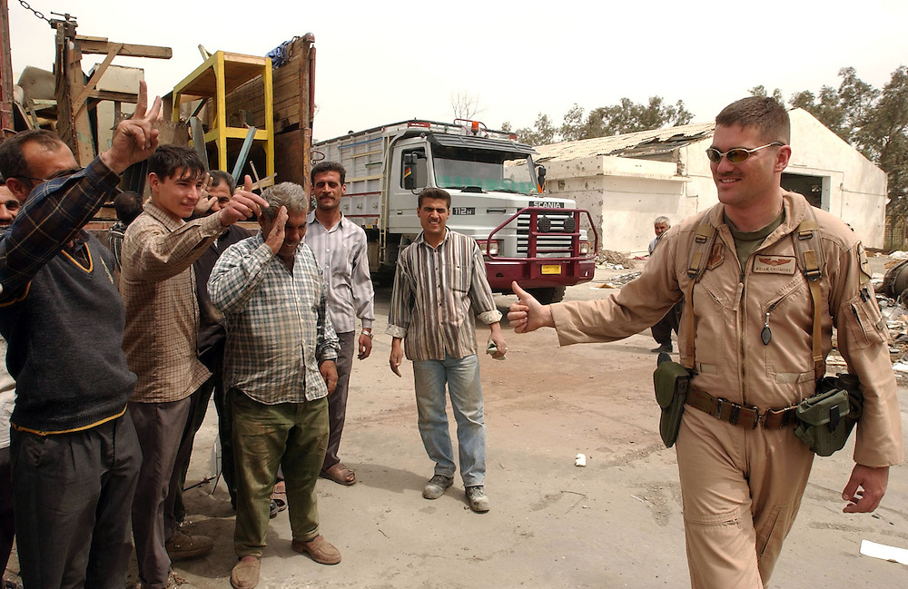 U. S. Air Force Capt. Brian Crismore, right, an A-10 pilot from the 332nd Expeditionary Fighter Squadron (from the 75th Fighter Squadron at Pope AFB, North Carolina), gives the thumbs up to a friendly group of Iraqi workers he met while surveying the Iraqi air base at Karkuk.  Crismore was part of a survey team sent to the base to assess it's use for A-10 fighters. The locals were hired to haul away scrap and debris from the Air Base.Capt. Crismore said one of the things he really wanted to do was meet some Iraqis so he went over and shook hands with these men.(Alan Lessig/Air Force Times)