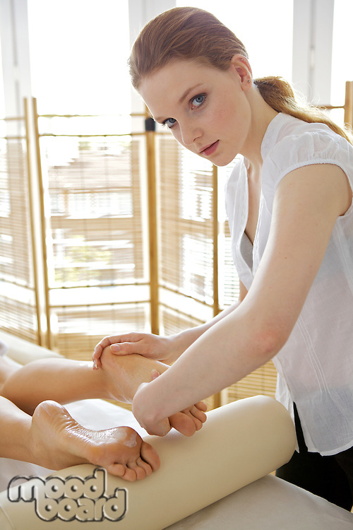 Young woman receiving foot massage from masseuse