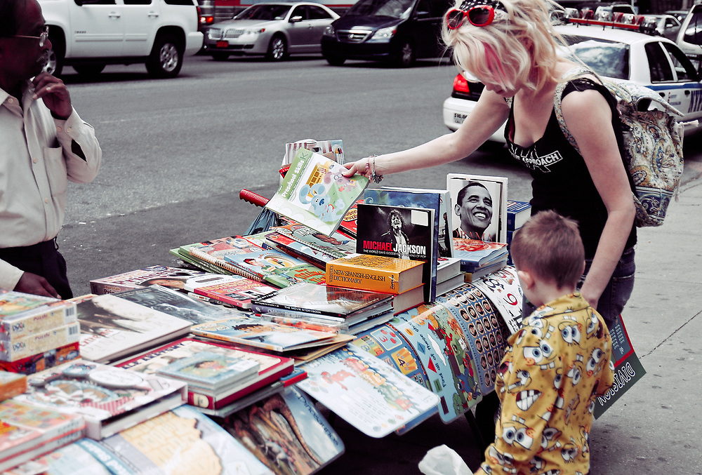 Mom and boy buying books on 42nd St. NYC 2011