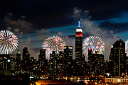 The Empire State Building, illuminated with red, white and blue lights is seen from across the East River during the Macy's Fourth of July fireworks show on Monday, July 4, 2011 in New York. (AP Photo/Kathy Kmonicek)
