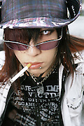A young cosplayer boy, smoking a cigarette and wearing sunglasses and coloured contact lenses. Harajuku, Tokyo, Japan September 2005