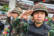 27 MAY 2014 - BANGKOK, THAILAND:  Thai soldiers stand at attention and salute while the Thai National Anthem is played at sundown. The soldiers were on crowd control duty in the wake of a coup. Several hundred people protested against the coup in Bangkok at Victory Monument. It was the fourth straight day of pro-democracy rallies in the Thai capital as the army continued to tighten its grip on Thai life. The protest Tuesday was the smallest so far.    PHOTO BY JACK KURTZ