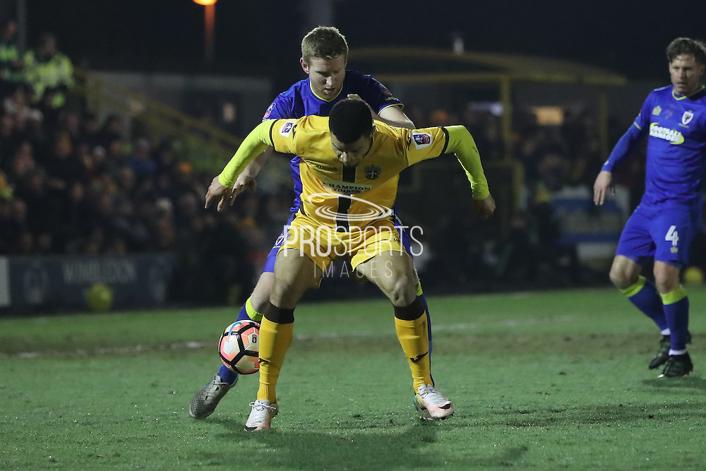 AFC Wimbledon defender Chris Robertson (34) gets up close with Sutton United Maxime Biamou (24) during the The FA Cup third round replay match between AFC Wimbledon and Sutton United at the Cherry Red Records Stadium, Kingston, England on 17 January 2017. Photo by Stuart Butcher.