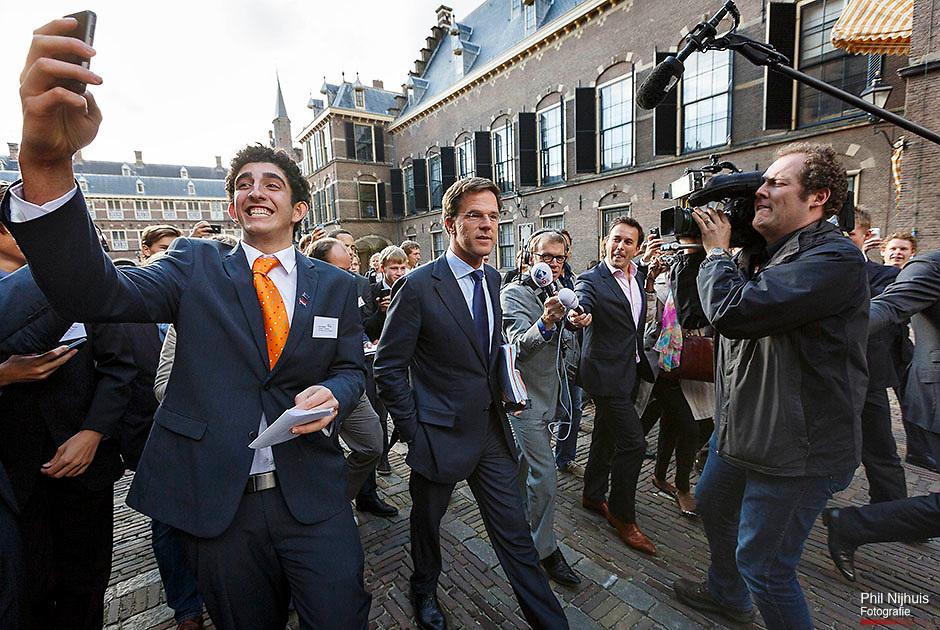 26 september 2012 Den Haag - Een jongen maakt een foto van zichzelf en premier Mark Rutte als hij over het Binnenhof loopt na afloop van de onderhandelingen met de informateurs en Pvda Onderhandelaar Samsom. Foto: Phil Nijhuis