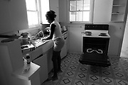 83777----  03.24.05 ----   Donesha Jackson does the dishes while the oven keeps the house warm on Church Street in McKinney, TX on March 24, 2005..Pastor Rock has spent the past three years fighting race, poverty  and violence at Sugar Hill, the poorest of the poor living in public housing in Texas' richest county, Collin County. Originating in 1969, the McKinney apartment complex rose next to an old cotton field, with 100 units that would battle decades of economic annd racial isolation, squalor, criminal neglect, crack cocaine and bureaucratic equivocation supported by millions of taxpayer dollars.