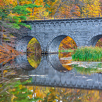 Wachusett Aqueduct Bridge framed by beautiful New England fall foliage reflecting in the Assabet River Reservoir in Northborough, Massachusetts on a brisk autumn day. <br />