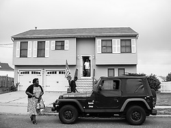 Daily Goodbye. Retired Sgt. Vidro watches his wife and son leave for a day of work and school.<br /> New Jersey, 2010.