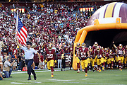 A member of the U.S. military runs onto the field carrying an American flag as he leads the Washington Redskins out of the tunnel and onto the field before their 2016 NFL week 1 regular season football game against the Pittsburgh Steelers on Monday, Sept. 12, 2016 in Landover, Md. The Steelers won the game 38-16. (©Paul Anthony Spinelli)