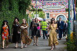 Ascot, UK. 20 June, 2019. A racegoer carries her high heels as she leaves barefoot from Royal Ascot after attending Ladies Day.