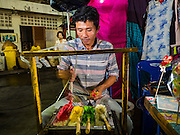 15 OCTOBER 2015 - BANGKOK, THAILAND: A candy maker creates sugar treats shaped like popular cartoon characters and flowers during the Vegetarian Festival at the Joe Sue Kung Shrine in the Talat Noi neighborhood of Bangkok. The Vegetarian Festival is celebrated throughout Thailand. It is the Thai version of the The Nine Emperor Gods Festival, a nine-day Taoist celebration beginning on the eve of 9th lunar month of the Chinese calendar. During a period of nine days, those who are participating in the festival dress all in white and abstain from eating meat, poultry, seafood, and dairy products. Vendors and proprietors of restaurants indicate that vegetarian food is for sale by putting a yellow flag out with Thai characters for meatless written on it in red.    PHOTO BY JACK KURTZ