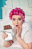 Portrait of shocked woman with chocolate lying on bed
