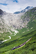 Andermatt, Switzerland, June 2012. A steam train of the DFB Dampfbahn Furka-Bergstrecke climbs through the spectacular landscape. The Glacier Express from Zermatt to St.Moritz also stops at Andermatt. There are roads in all four cardinal directions to Andermatt, and being a bit off the beaten track, driving there may be an alternative. The town is surrounded by mountain passes, and you need to cross at least one in order to get into the town. The highest of them, Furka to the west is situated at more than 2400 meters and he Andermatt itself more than 1400 meters (almost one mile) over the sea level. Driving through alpine passes is a great experience and the views are fantastic.By taking the train to reach the highest railway stations of Europe, we get the trailheads for some spectacular high alpine hikes. Photo by Frits Meyst/Adventure4ever.com